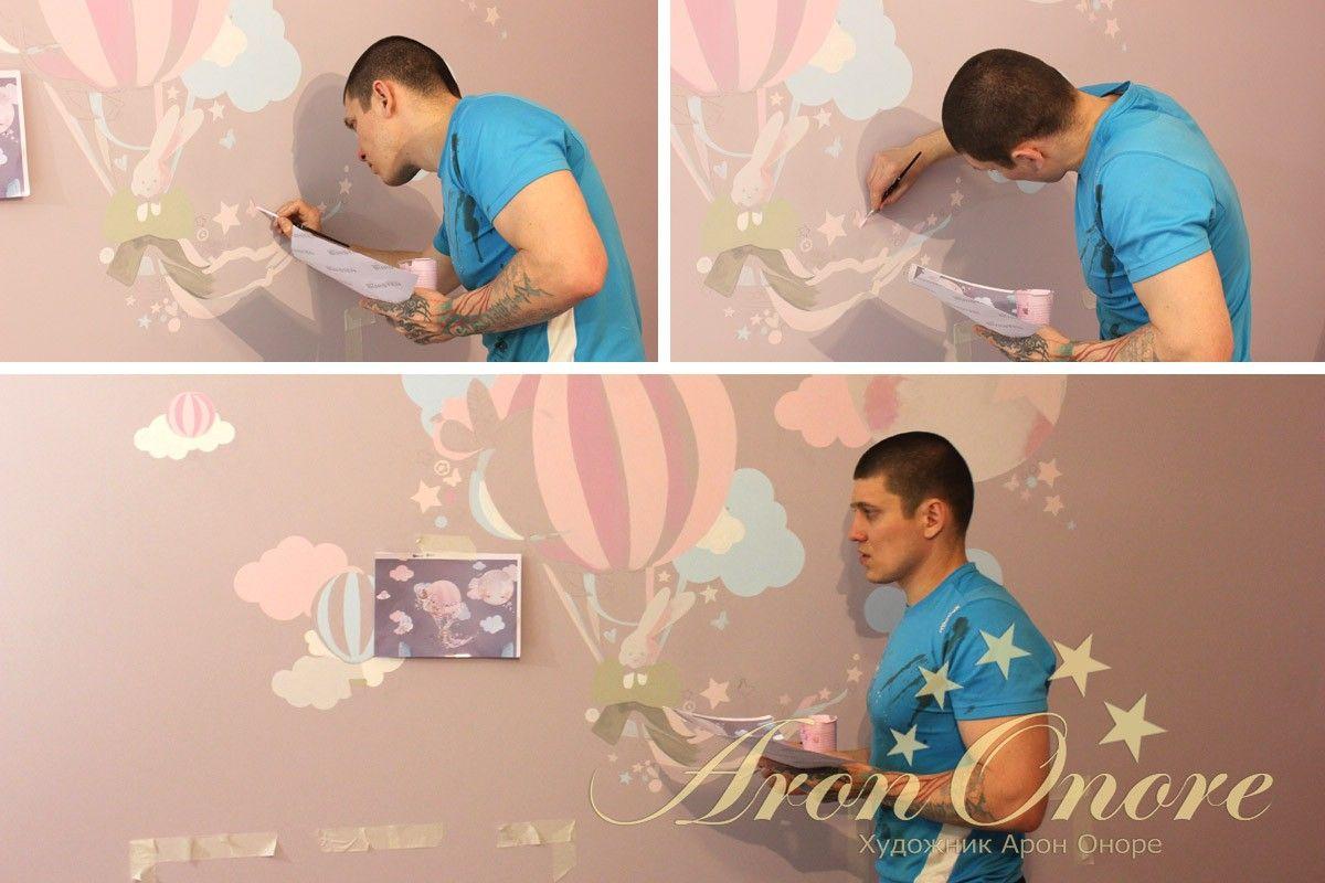 художник рисует в детской роспись на стене