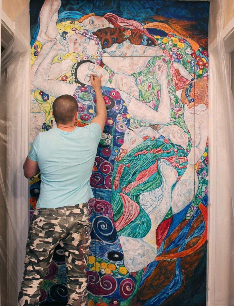 Художник рисует роспись на двери.