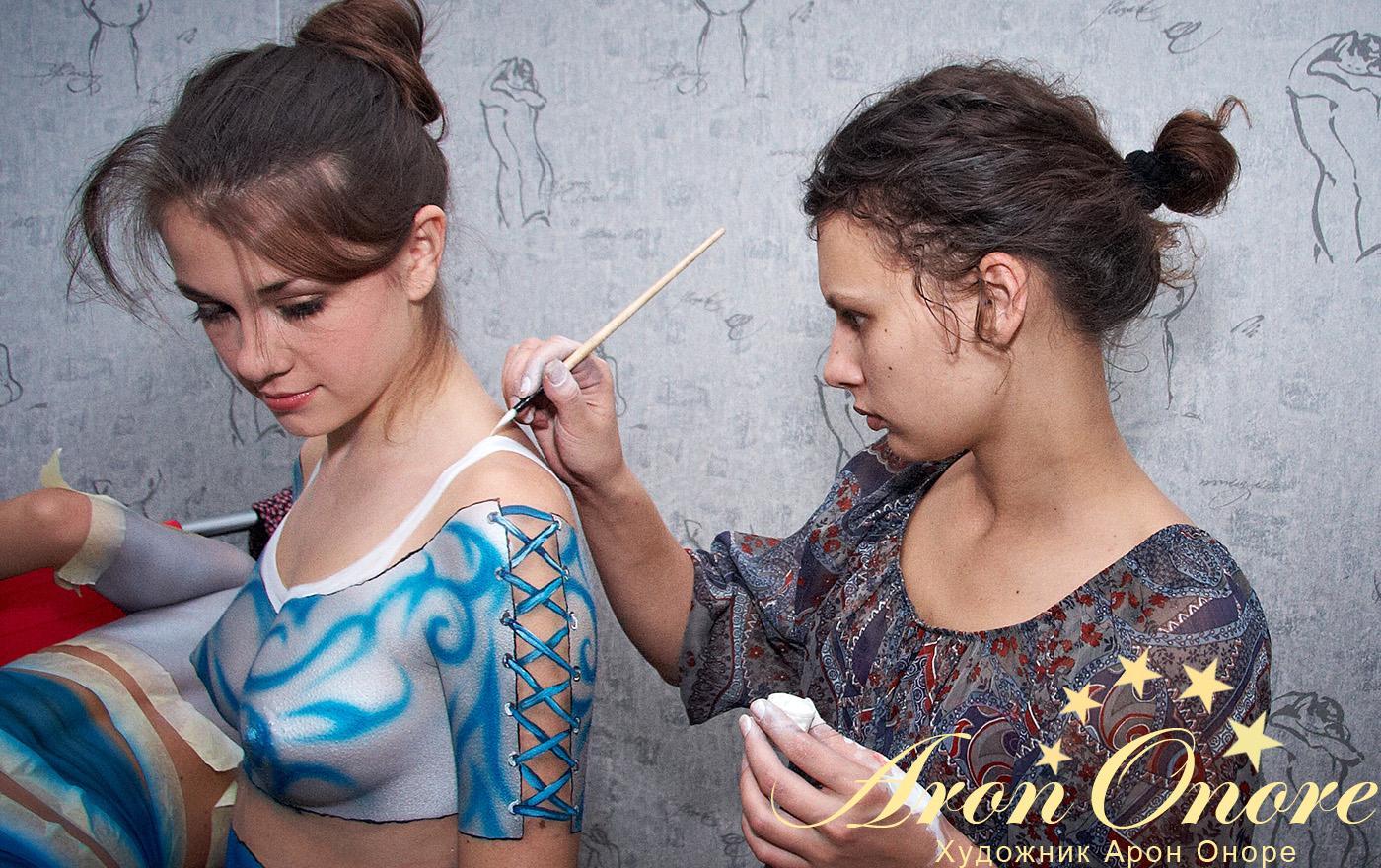 Художник занимается созданием рисунка на теле красивой девушки